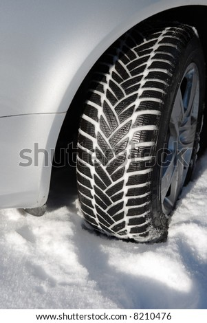 winter tire, tread filled with snow, on car with silver colored fender - stock photo