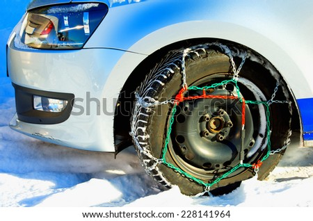 Winter tire with colorful chains on car on snow