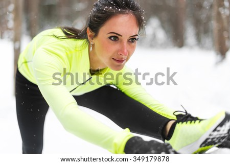 Winter training Fitness model athlete girl warm up stretching her hamstrings, leg and back - stock photo