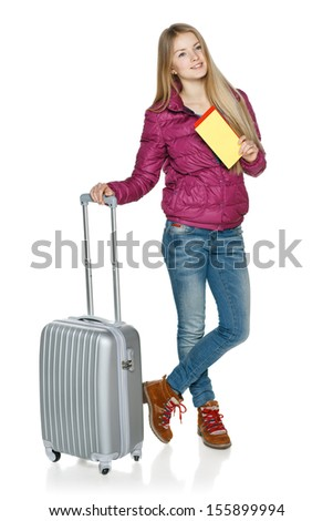 Winter traveler. Daydreaming young female in winter jacket in full length standing with the suitcase and blank tickets, looking to the side, isolated on white background - stock photo