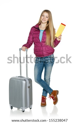 Winter traveler. Full length of young female in winter jacket standing with the suitcase showing blank tickets, isolated on white background