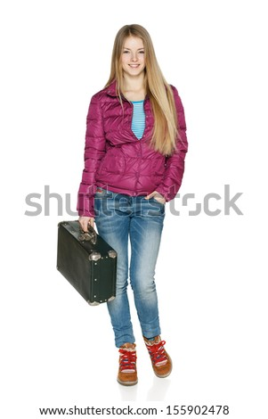 Winter traveler. Smiling young female in winter jacket in full length standing with the old fashioned suitcase, isolated on white background - stock photo