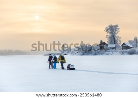 Winter travelers hiking on lake ice at sunset over village - stock photo