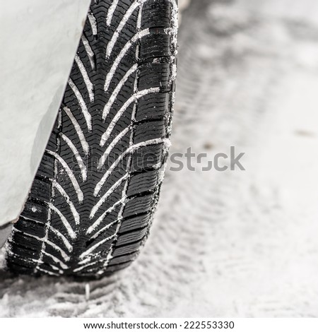 Winter tyre on snowy road - stock photo