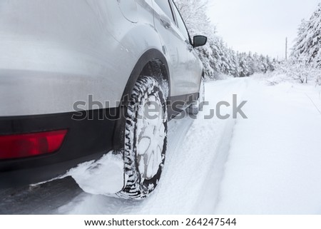 Winter tyres wheels of car on snowy country road - stock photo