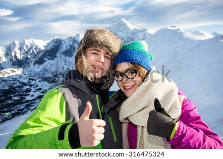 Winter vacation - girl and boy in mountain - stock photo