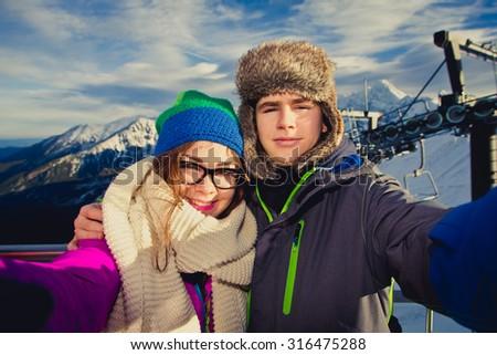 Winter vacation - teens in mountains - stock photo