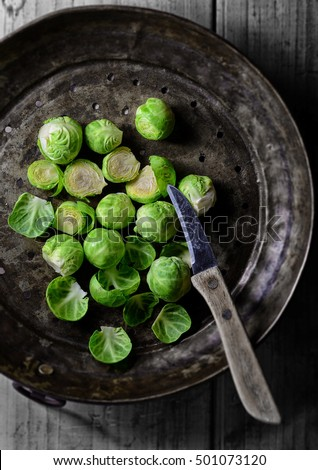 Winter vegetables. Brussels sprouts prepared for cooking on rustic metal dish. Country kitchen look with selective focus. Top view.