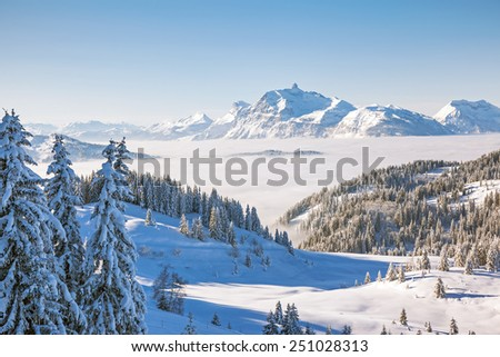Winter view from the slopes of Les Gets in the Portes du Soleil ski area, France. The distinctive peak of Pointe Percee in the Aravis mountain range can be seen in the background.