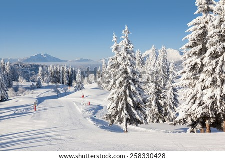 Winter view of an empty ski slope in Les Gets - part of the Portes du Soleil ski area, France. - stock photo