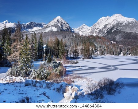 Winter view of frozen surface of Strbske Pleso (Tarn) and peaks High Tatra mountains in background. Strbske Pleso is second largest glacial lake on the Slovak side of the High Tatra Mountains. - stock photo