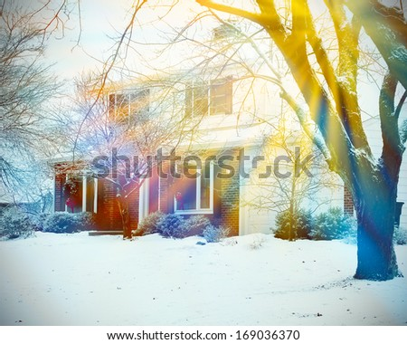 Winter view of house with snow and sunlight - stock photo