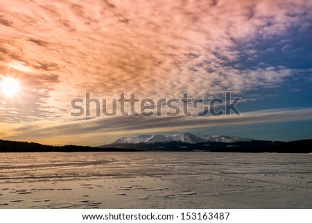 winter view of lake and mountains with a beautiful sky in the background