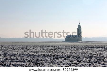 winter view of lonely rural church on the field - stock photo