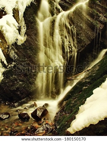 Winter view to cascade of waterfall, icy snow on the rocky wall and boulders in rapid stream. Reflections of light on ice and wet stones.  - stock photo