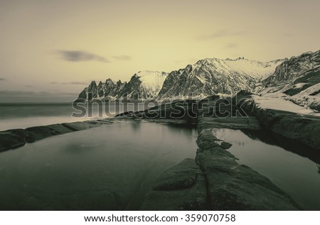 Winter view to Steinfjord on Senja island in the sunset - Troms county, Norway (long exposure, stylized retro) - stock photo