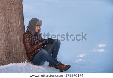 Winter walk - young man in an ear flap hat sitting under a tree - stock photo