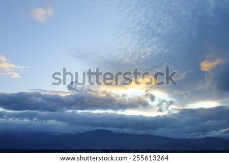 Winter weather system with rain clouds above Mojave desert south edge, Indio, California; backlit shot - stock photo
