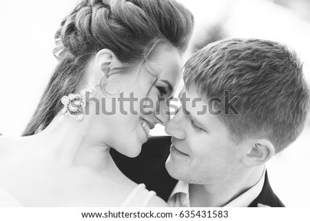 Winter wedding outdoors on snow background. Bride and groom are standing and hugging.