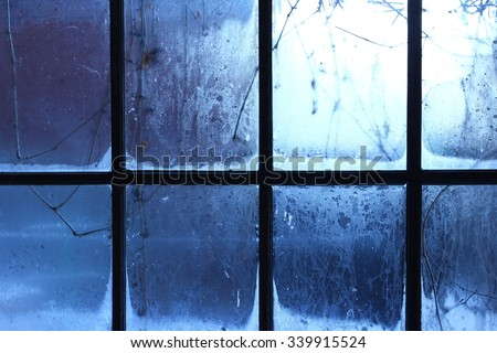 Winter window, drops of water and snowflakes on a window pane. - stock photo