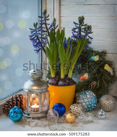 Winter window on the eve of holidays with a lantern, wreath and Christmas toys