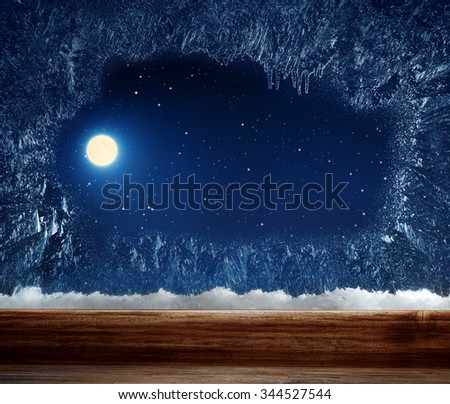Winter window with frosted inside. Outside stars and the moon. - stock photo