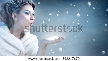 Winter woman  blowing snow over blue background - snow queen - stock photo