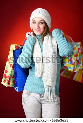 Winter woman carrying colorful shopping bags