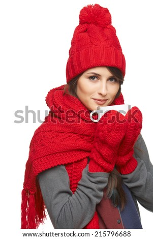 Winter woman drinking tea wearing warm winter clothing, hat, gloves and scarf, over white background - stock photo
