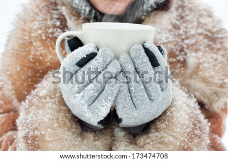 Winter woman holding a mug to get warm - stock photo