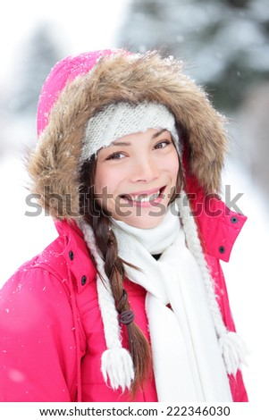 Winter woman in snow outside in nature. Portrait closeup outdoors in snow. Happy beautiful smiling multicultural Asian Caucasian girl. - stock photo