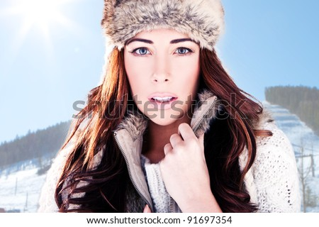 Winter Woman On Ski Slope. Close-up head-shot of a beautiful woman dressed in winter fur with a mountain ski slope background - stock photo