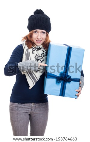 Winter woman pointing at big present, isolated on white background. - stock photo