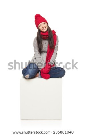 Winter woman wearing knitted warm red scarf, hat and socks sitting on big white box, over white background - stock photo