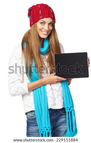 Winter woman wearing warm knitted hat and scarf showing tablet screen smiling isolated on white background - stock photo