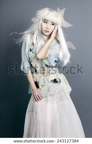 Winter women Portrait. Snow. Young beautiful fashion Model woman with White Hair. Make up. Asia face Snow Queen - stock photo