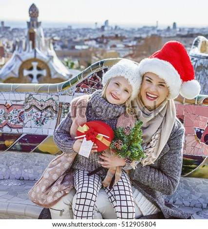 Winter wonderland in Barcelona at Christmas. Portrait of happy trendy mother and child travellers with a little Christmas tree and present box at Guell Park in Barcelona, Spain