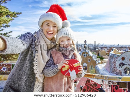 Winter wonderland in Barcelona at Christmas. Portrait of happy trendy mother and daughter travellers with a little Christmas tree and present box at Guell Park in Barcelona, Spain taking selfie
