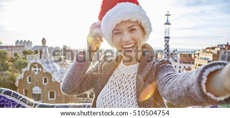 Winter wonderland in Barcelona at Christmas. Portrait of smiling trendy traveller woman in a Santa hat at Guell Park in Barcelona, Spain taking selfie