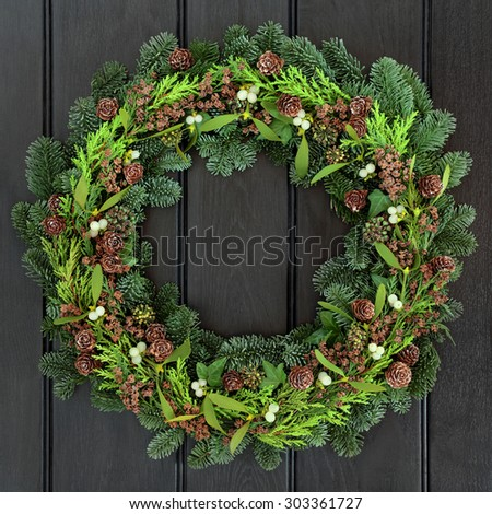 Winter wreath with mistletoe and blue spruce fir over dark blue oak front door background.