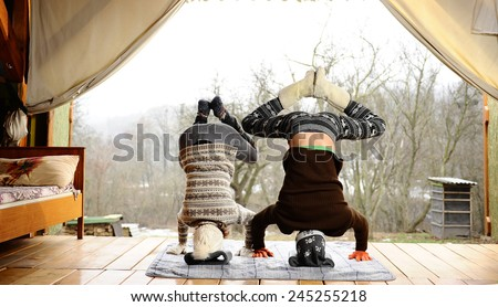 winter yoga on the porch of a country house. - stock photo