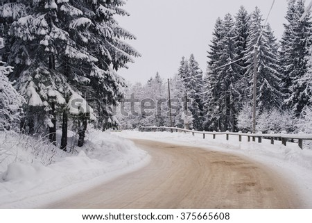 Winters road following in the snow forest - stock photo