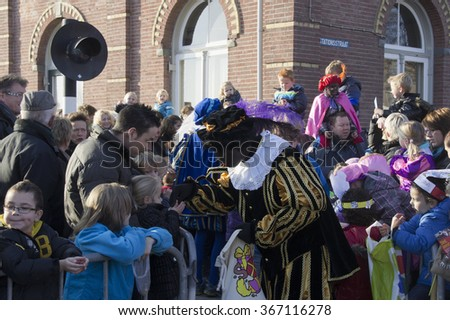 WINTERSWIJK, THE NETHERLANDS - 12 NOVEMBER 2011: Black Peter gives candy to the children on 12 November  2011 in Winterswijk, Holland. - stock photo