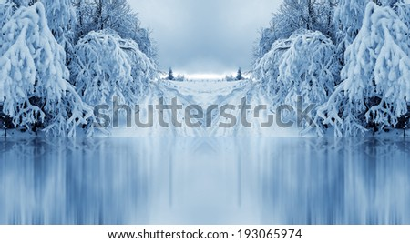 wintertime lake covered with ice among the abundantly snowy trees - stock photo