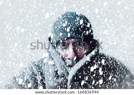 Wintery scene of shivering man in snowstorm or ice storm  - stock photo