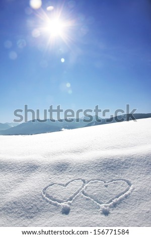 wintry bavarian landscape with love hearts and bright sunshine with flares - stock photo
