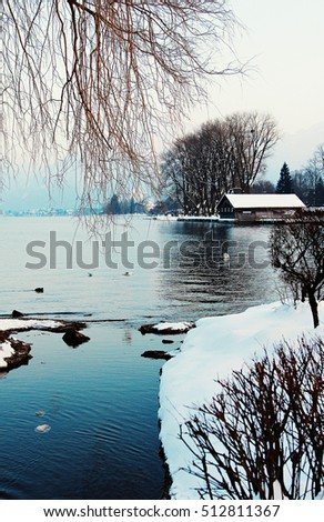 wintry lake tegernsee with boathouse and overhanging branches
