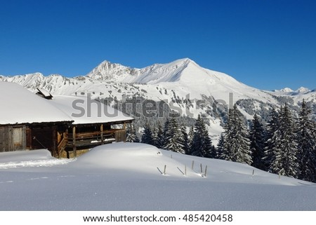 Wintry landscape in Gstaad, Swiss Alps. View from Mt Hohe Wispile. Snow covered Mt Lauenenhorn. Traditional timber hut.