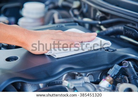 Wipe cleaning the car engine with gray microfiber cloth - stock photo