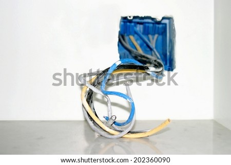 Wire box with different colored cables for power outlet installation.